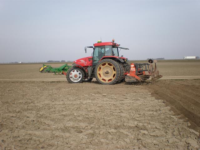 Voordat de pootmachine de aardappelen in de grond kan stoppen, wordt het land bewerkt.